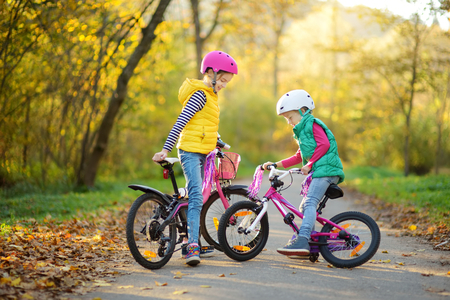Cute little sisters riding bikes in a city park on sunny autumn day. Active family leisure with kids. Children wearing safety hemet while riding a bicycle.
