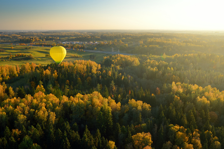 Colorful hot air balloon flying over forests surrounding Vilnius city on sunny autumn evening. Vilnius is one of the few European capital cities, where hot air balloons are allowed to fly.