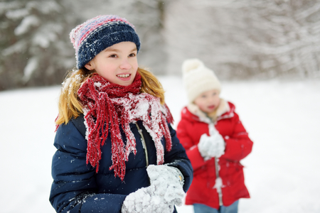 Two adorable little girls having fun together in beautiful winter park. Beautiful sisters playing in a snow. Winter activities for kids. Stock Photo
