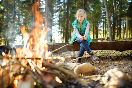 Cute little girl roasting hotdog on a stick at bonfire. Child having fun at camp fire. Camping with kids in fall forest. Family leisure with kids at autumn.