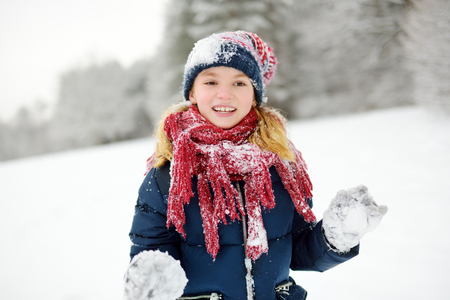 Adorable little girl having fun in beautiful winter park. Cute child playing in a snow. Winter activities for kids