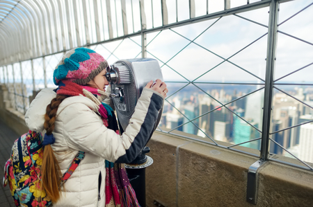 Happy young woman tourist at the observation deck of Empire State Building in New York City. Female traveler enjoying the view of NYC skyline. Travelling in USA.