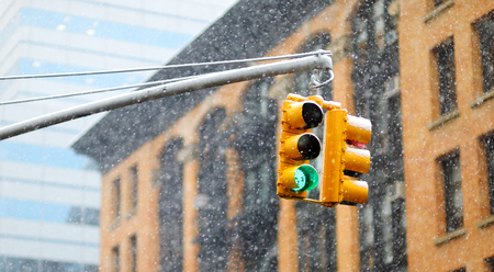 New York city traffic lights with skyscrapers on background during massive snowfall. Travelling in USA.
