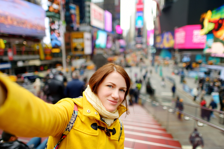 Heureuse jeune femme visites touristiques à Times Square à New York. Voyageuse prenant des selfies avec son smartphone dans le centre-ville de Manhattan. Voyager aux USA.