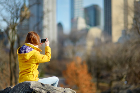 Happy young woman tourist taking pictures at Central Park in New York City. Female traveler enjoying views of downtown Manhattan. Travelling in USA. Stok Fotoğraf