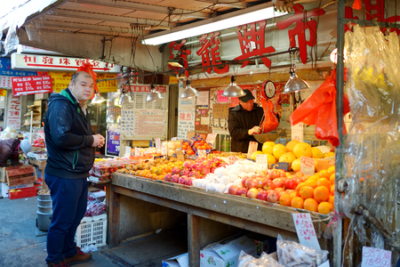 NEW YORK - MARCH 21, 2015: Customer buying fruits in Chinese store in Chinatown district of New York City, one of oldest Chinatowns outside Asia.