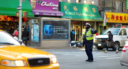 NEW YORK - MARCH 21, 2015: NYPD officer regulating traffic in Chinatown district of New York City, one of oldest Chinatowns outside Asia.