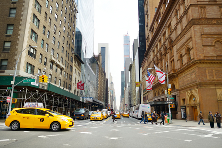 NEW YORK - MARCH 16, 2015: Yellow taxi cabs and people rushing on busy streets of downtown Manhattan. Taxicabs with their distinctive yellow paint are a widely recognized icon of New York City.