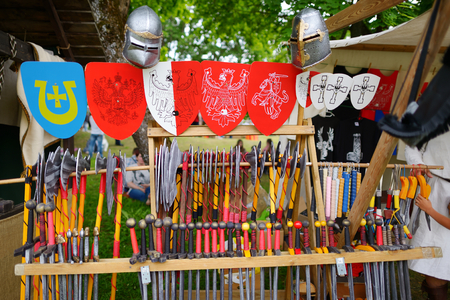 TRAKAI, LITHUANIA - JUNE 16, 2018: Toy medieval armour, helmets and wooden weapons sold on market stall during annual Medieval Festival, held in Trakai Peninsular Castle. Standard-Bild - 114718226