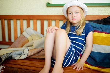 Jolie petite fille portant un chapeau de paille s'amusant dans la cour le soir d'été ensoleillé. Activités estivales pour les enfants.