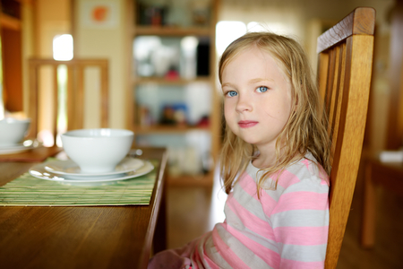 Cute little girl eating a soup in cozy dining room. Child having a dinner at home. Healthy nutrition for small kids.