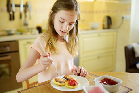 Cute little girl enjoying her breakfast at home. Pretty child eating pancakes with strawberry sauce before school. Healthy nutrition for children.