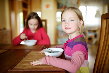 Two cute little sisters eating a soup in cozy dining room. Children having a dinner at home. Healthy nutrition for small kids.