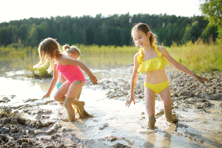 Three young sisters taking healing mud baths on lake Gela near Vilnius, Lithuania. Children having fun with mud. Kids playing with medicinal clay. Standard-Bild