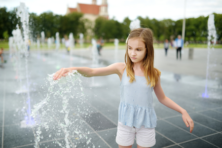 Cute preteen girl playing in fountains on newly renovated Lukiskes Square in Vilnius, Lithuania. Child having fun with water on sunny summer day. Active leisure for kids.