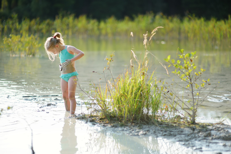 Young girl taking healing mud baths on lake Gela near Vilnius, Lithuania. Child having fun with mud. Kid playing with medicinal clay. Stockfoto