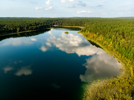 Aerial top down view of beautiful green waters of lake Gela. Birds eye view of scenic emerald lake surrounded by pine forests. Clouds reflecting in Gela lake, near Vilnius city, Lithuania. 版權商用圖片