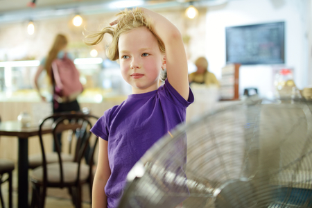 Cute little girl standing in front of a fan on hot summer day. Child enjoying cool wind in summer season. Hot weather conditions. Reklamní fotografie