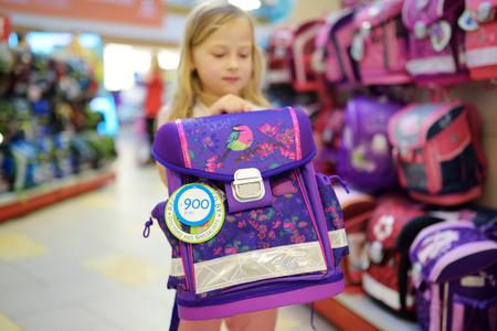 Cute dziewczynka wybierając tornister przed rozpoczęciem zajęć. Urocza uczennica kupująca szkolny plecak w sklepie. Powrót do koncepcji szkoły. Zdjęcie Seryjne