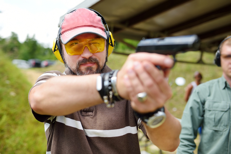 Man shooting on an outdoor shooting range. Male aiming gun at firing range. Active leisure.
