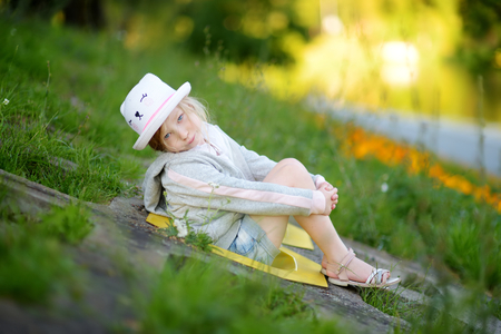 Cute little girl having fun outdoors on sunny summer evening. Child exploring nature. Summer activities for kids.