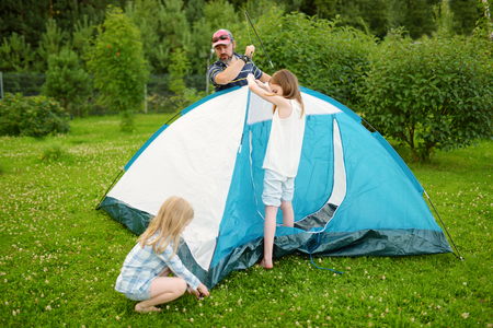 Cute little girls helping their parent to set up a tent on a campsite. Active lifestyle, family recreational weekend, summer outdoor.
