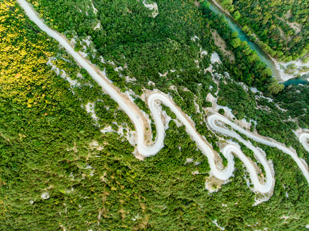 Aerial top down view of serpentine narrow road leading to Vikos Gorge in Northern Greece. A road full of twists and turns winding sharply up the mountain in Zagori region, Greece. Stock Photo