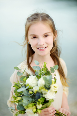 Adorable little bridesmaid holding beautiful flower bouquets after wedding cemerony outdoors. Destination wedding on Cephalonia island on Greece.