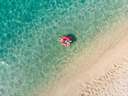 Aerial top down view of cute young girl floating on toy ring at Myrtos beach, the most beautiful beach of Kefalonia, a large coast with turqoise water and white coarse sand. Cephalonia, Greece. Imagens