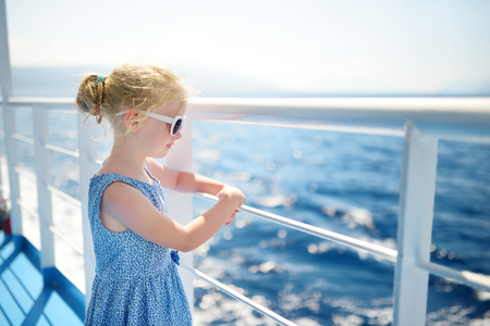 Adorable young girl enjoying ferry ride staring at the deep blue sea. Child having fun on summer family vacation in Greece. Kid sailing on a boat. Imagens