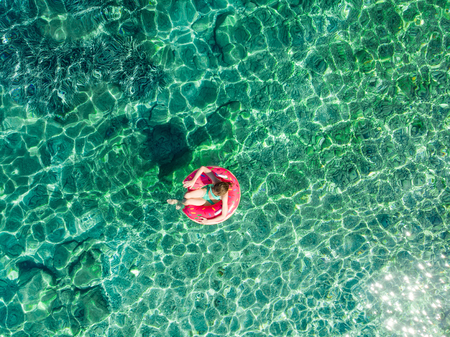 Aerial top down view of cute young girl floating on toy ring at Emplisi Beach, picturesque stony beach in a secluded bay, with clear waters popular for snorkelling. Kefalonia, Greece.