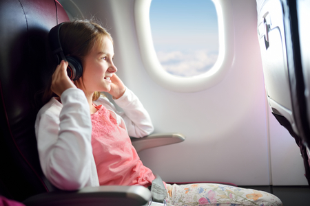 Adorable young girl traveling by an airplane. Child sitting by aircraft window and looking outside while listening to music. Traveling abroad with kids.