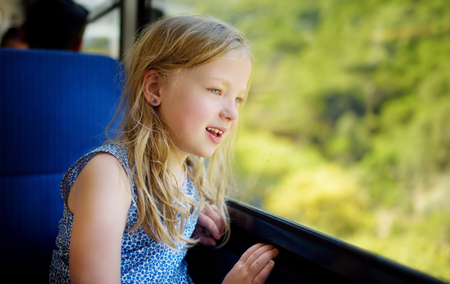 Cute young girl traveling by train on summer day. Child sitting by the window of railway wagon and looking outside. Kid on family vacation in Europe. Imagens