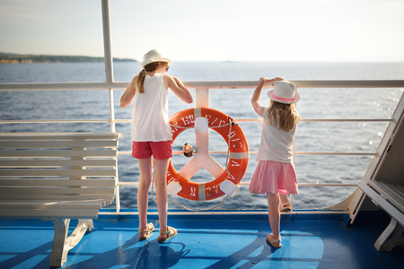 Adorable young girls enjoying ferry ride staring at the sea on sunset. Children having fun on summer family vacation in Greece. Kid sailing on a boat. 版權商用圖片