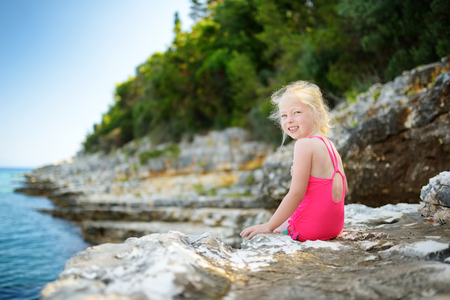 Cute little girl having fun at Emplisi Beach, picturesque stony beach in a secluded bay, with clear waters popular for snorkelling. Small pebble beach near Fiscardo town of Kefalonia, Greece.