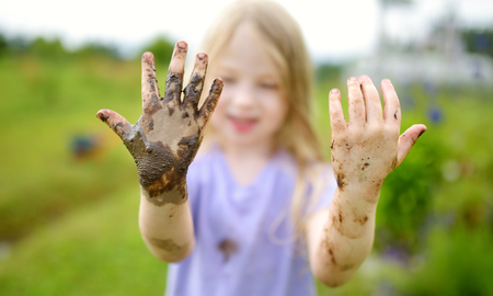 Funny little girl playing in a large wet mud puddle on sunny summer day. Child getting dirty while digging in muddy soil. Messy games outdoors. Stock Photo - 119881263