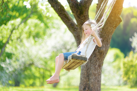 Cute little girl having fun on a swing in blossoming old apple tree garden outdoors on sunny spring day. Spring outdoor activities for kids. 免版税图像