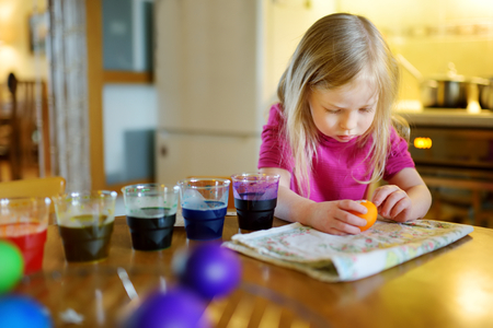 Cute young girl dyeing Easter eggs at home. Child painting colorful eggs for Easter hunt. Kid getting ready for Easter celebration. Family traditions.