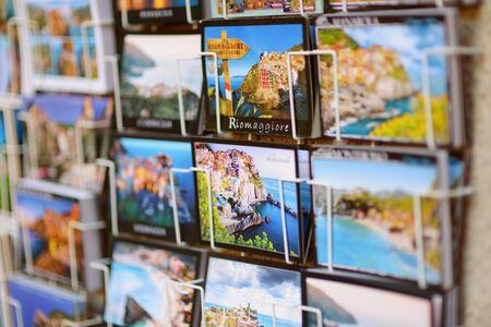 CORNIGLIA, ITALY - NOVEMBER 20, 2018: Various postcards from Cinque Terre displayed at souvenir shop Standard-Bild - 128986438