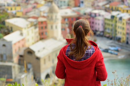 Young female tourist enjoying the view of Vernazza, one of the five centuries-old villages of Cinque Terre, located on rugged northwest coast of Italian Riviera, Liguria, Italy. Stok Fotoğraf