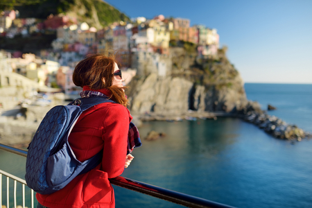 Young female tourist enjoying the view of Manarola, one of the five centuries-old villages of Cinque Terre, located on rugged northwest coast of Italian Riviera, Liguria, Italy. Traveling off season.