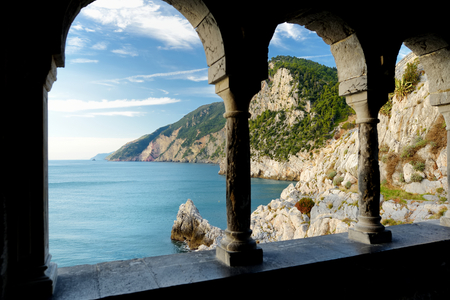 Columns of famous gothic Church of St. Peter (Chiesa di San Pietro) with beautiful shoreline scenery in Porto Venere village on the Ligurian coast of northwestern Italy