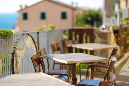 Pequeñas mesas de restaurante al aire libre bellamente decoradas en la aldea de Riomaggiore, Cinque Terre, Liguria, Italia