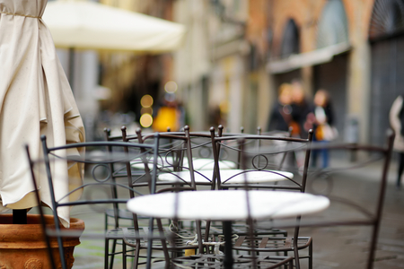 Empty small outdoor restaurant tables on the main square of Lucca, Tuscany, Italy Imagens