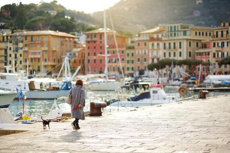 Femme promenant son chien dans la marina de la ville de Santa Margherita Ligure, située dans la ville métropolitaine de Gênes, Ligurie, Italie Banque d'images