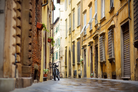 Bicycles parked on beautiful medieval streets of Lucca city, known for its intact Renaissance-era city walls, Tuscany, Italy. 免版税图像