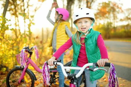 Cute little sisters riding bikes in a city park on sunny autumn day. Active family leisure with kids. Children wearing safety helmet while riding a bicycle. Stockfoto