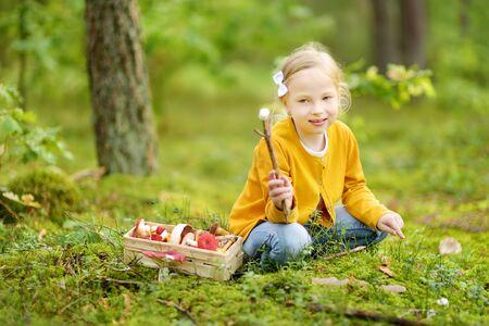 Cute młoda dziewczyna zabawy podczas wędrówki po lesie w piękny letni dzień. Dziecko odkrywania przyrody. Aktywny wypoczynek rodzinny z dziećmi.