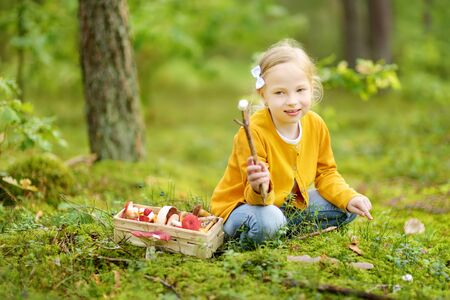 Cute young girl having fun during forest hike on beautiful summer day. Child exploring nature. Active family leisure with kids.