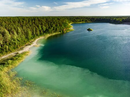 Aerial view of beautiful green waters of lake Gela. Birds eye view of scenic emerald lake surrounded by pine forests. Clouds reflecting in Gela lake, near Vilnius city, Lithuania.